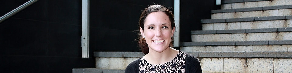 Siobhan Kelly smiles in front of a set of concrete stairs