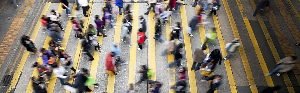 People cross a busy street in Hong Kong