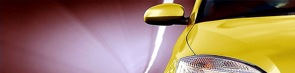 Front of a yellow car driving through a tunnel, right front light and wing mirror in view