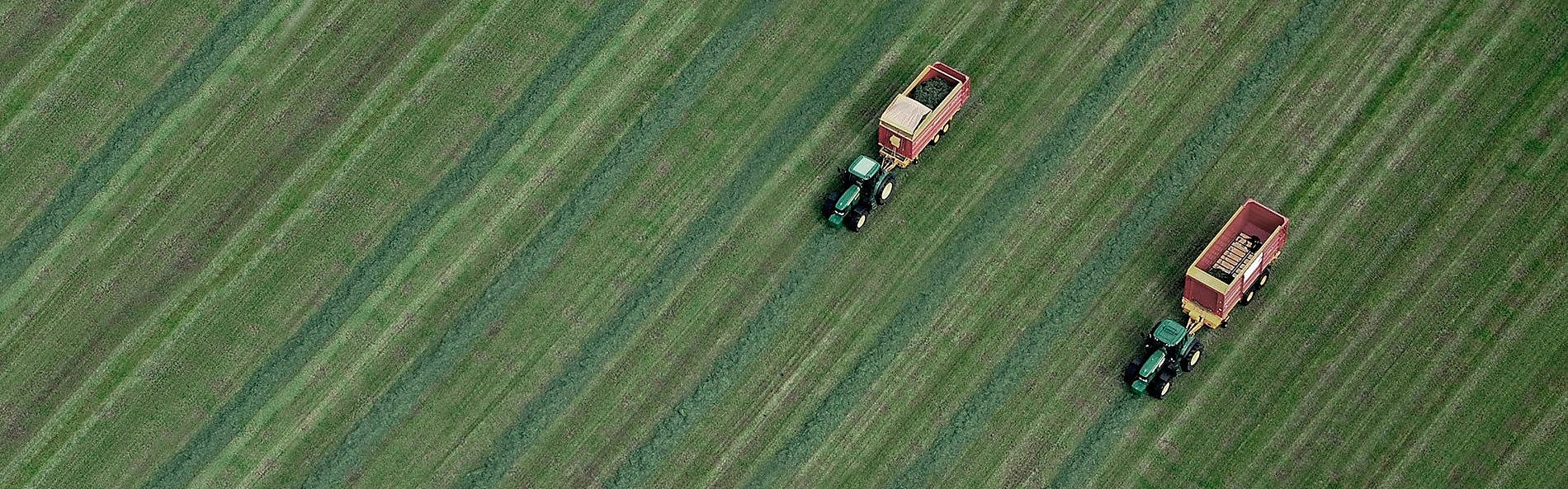 two tractors in a green field pictured from above